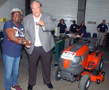 image of grand prize winner receiving key to riding lawn mower