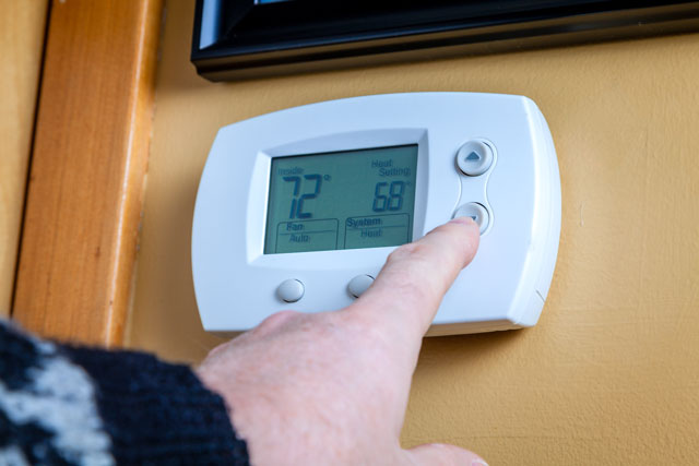 image of man adjusting settings of a digital thermostat